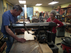 Volunteer carpenter teaching a woman how to use the saw to cut wood for a coffin.